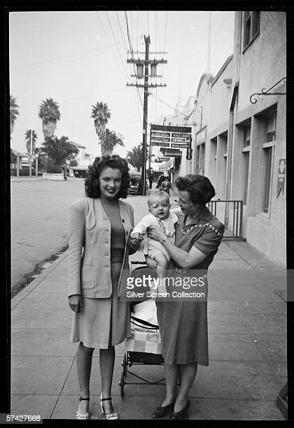Norma Jeane Baker future film star Marilyn Monroe in the street with a mother and baby circa 1941