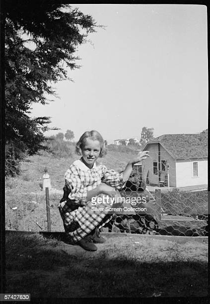Norma Jeane Baker future film star Marilyn Monroe playing with dogs in a rural garden circa 1933