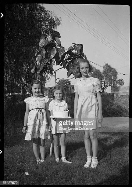Norma Jeane Baker future film star Marilyn Monroe with two small friends and a birthday cake circa 1936