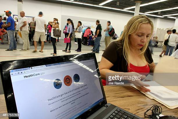Norma Licciardello sits with an agent from Sunshine Life and Health Advisors as they wait for the Affordable Care Act website to come back on line as...