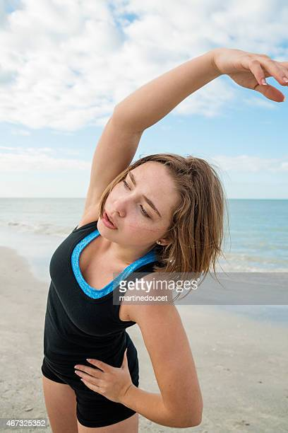 Normal looking young woman exercising on the beach.