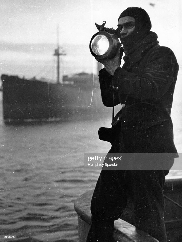 Norman Bricknat uses an Aldis Lamp to signal instructions to other minesweepers on a morning patrol off the north-east coast. Original Publication: Picture Post - 230 - A Day On A Minesweeper - pub. 1940