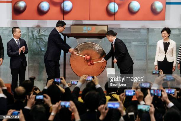 Norman Chan chief executive of the Hong Kong Monetary Authority second left and Pan Gongsheng deputy governor of the People's Bank of China second...