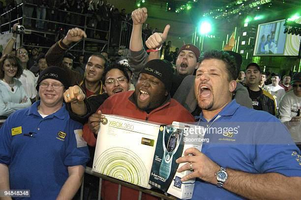 Norman Edwards, center, celebrates being the first person to purchase the new Microsoft Xbox 360 video-game console at the Zero Hour event in...