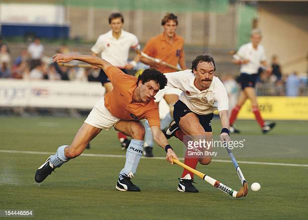 Norman Hughes of England makes a tackle on Hendrik Jan Kooijman of the Netherlands during their match at the 6th FIH Men's Field Hockey World Cup on...