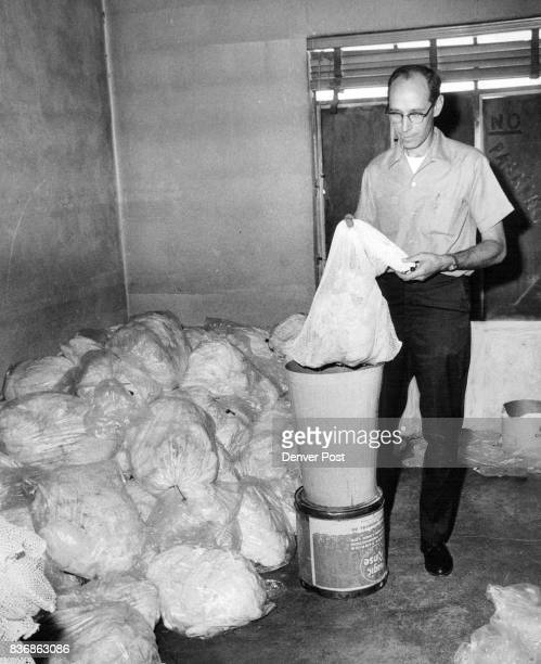 Norman Kopplinger of Small Fry Diaper Service removes dirty diapers from plastic bags to net for washing That's one day's collection of dirty diapers...