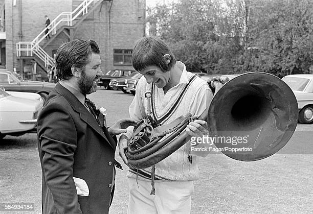 Norman McVicker of Leicestershire with a helicon musical instrument and a spectator during the John Player League match between Leicestershire and...