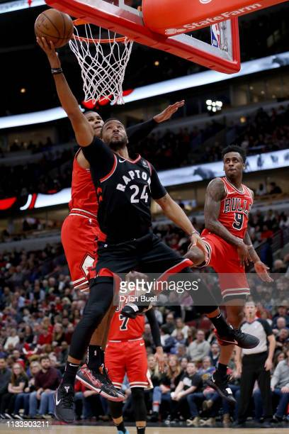Norman Powell of the Toronto Raptors attempts a shot past Cristiano Felicio of the Chicago Bulls in the second quarter at the United Center on March...