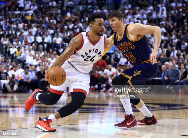 Norman Powell of the Toronto Raptors dribbles the ball as Kyle Korver of the Cleveland Cavaliers defends in the second half of Game Four of the...