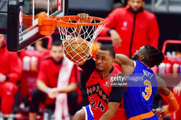Norman Powell of the Toronto Raptors dunks the ball against Nerlens Noel of the New York Knicks during the first half of a game at Amalie Arena on...