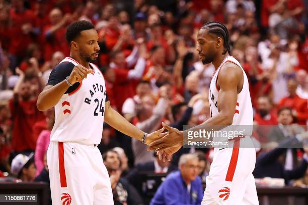 Norman Powell of the Toronto Raptors high fives Kawhi Leonard during the second half against the Milwaukee Bucks in game four of the NBA Eastern...