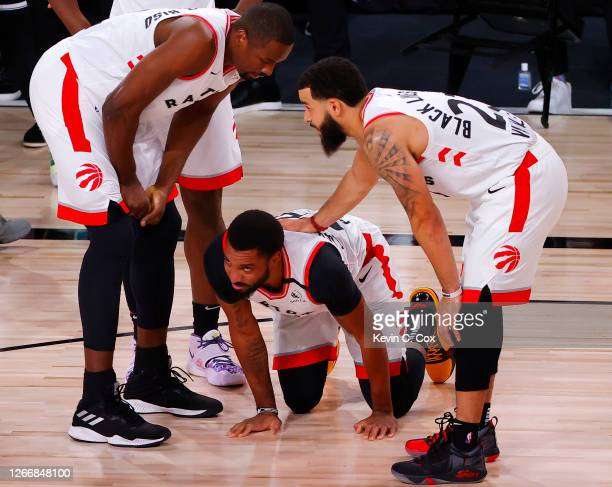 Norman Powell of the Toronto Raptors is helped up by teammates Serge Ibaka and Fred VanVleet against the Brooklyn Nets during the first quarter in...