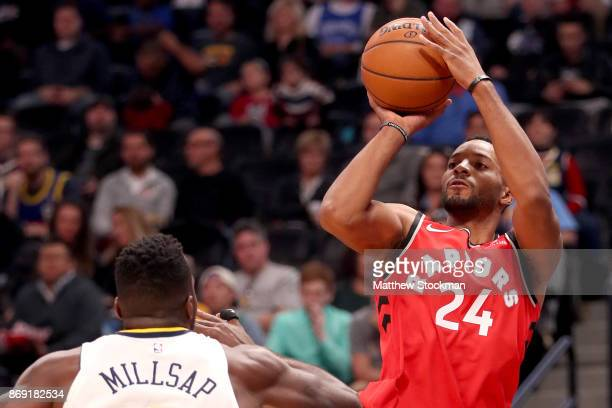 Norman Powell of the Toronto Raptors puts up a shot of Paul Millsap of the Denver Nuggets at the Pepsi Center on November 1 2017 in Denver Colorado...