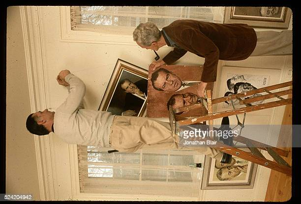 Norman Rockwell smokes a pipe as he helps hang his art in the Norman Rockwell Museum at the corner house in Stockbridge Massachusetts A man on a...