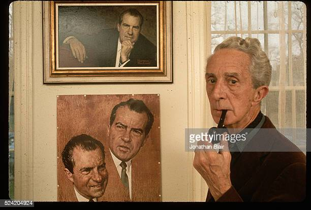 """Norman Rockwell smokes a pipe as he stands next his portraits of Richard Nixon in the Norman Rockwell Museum at the """"corner house"""" in Stockbridge,..."""