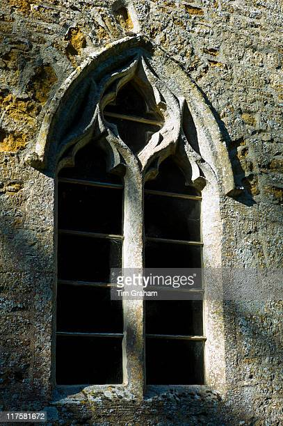 Norman style old stone window at 11th Century St Nicholas Church Oddington near Stow on the Wold Gloucestershire
