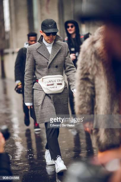 Norman Tan wears a cap sunglasses a gray coat a Gucci bag under the rain outside Paul Smith during Paris Fashion Week Menswear Fall Winter 20182019...