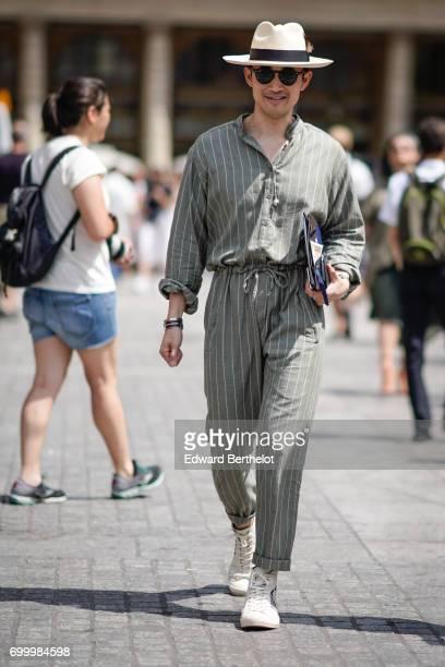 Norman Tan wears a hat sunglasses a striped shirt striped pants white sneakers outside the Louis Vuitton show during Paris Fashion Week Menswear...