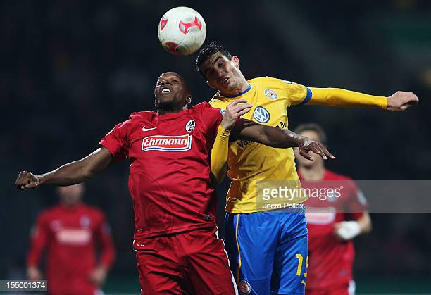 Norman Theuerkauf of Braunschweig and Karim Guede of Freiburg compete for the ball during the second round DFB Cup match between Eintracht...