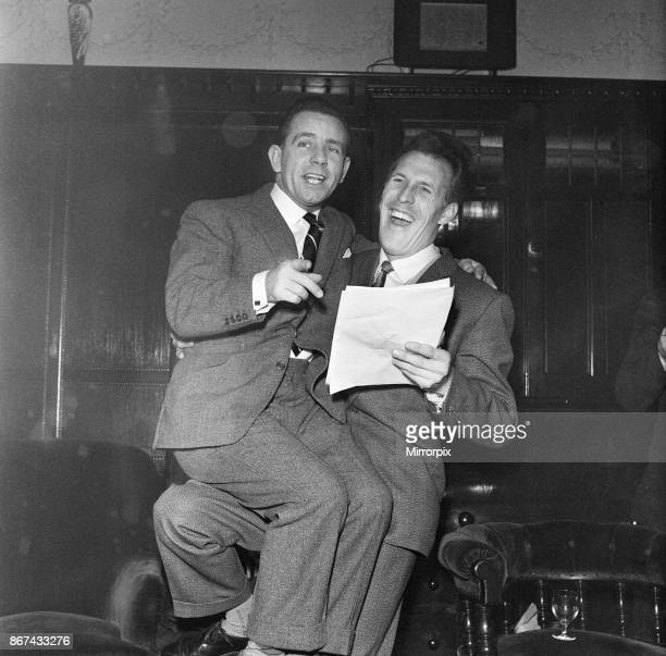 Norman Wisdom sits on Bruce Forsyth's knee and looks at the script for a pantomime which Norman is to appear in at christmas time November 1959