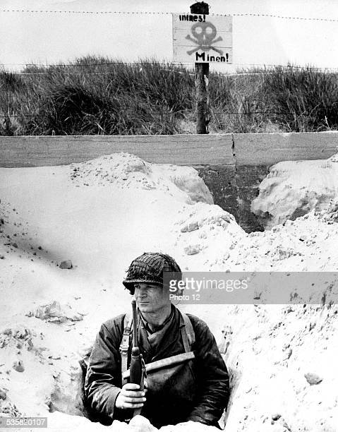 An American soldier hidden in a trench watches the beach Above him the German placard reads that the area is mined June 1944 France Second World War...