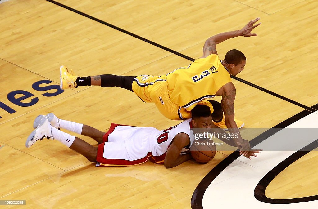 Norris Cole #30 of the Miami Heat dives for a loose ball against George Hill #3 of the Indiana Pacers in overtime during Game One of the Eastern Conference Finals at AmericanAirlines Arena on May 22, 2013 in Miami, Florida.