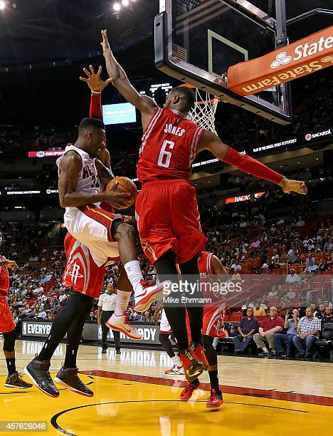 Norris Cole of the Miami Heat drives on Terrence Jones of the Houston Rockets during a preseason game at American Airlines Arena on October 21 2014...