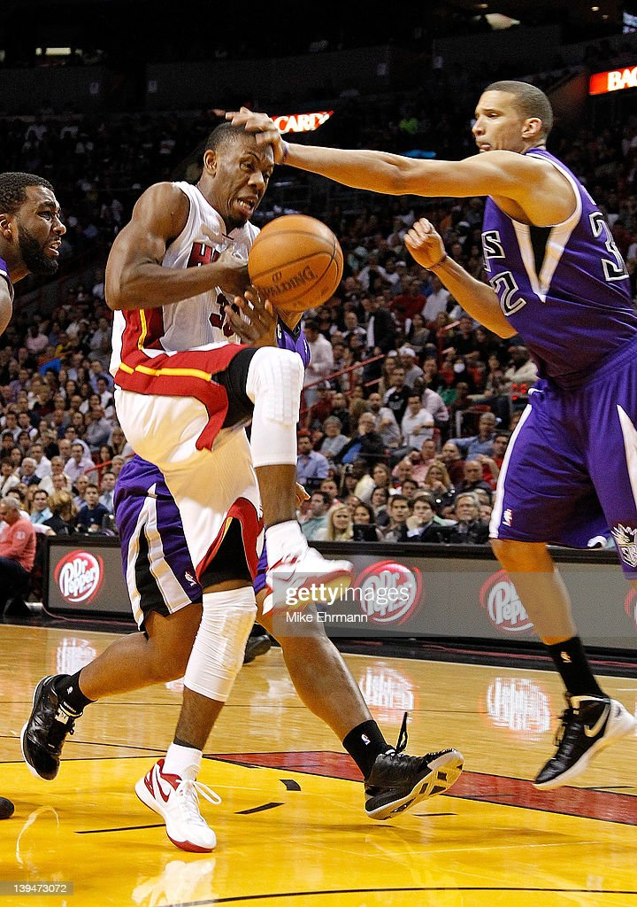 Norris Cole #30 of the Miami Heat is fouled driving to the basket by Francisco Garcia #32 of the Sacramento Kings during a game at American Airlines Arena on February 21, 2012 in Miami, Florida.