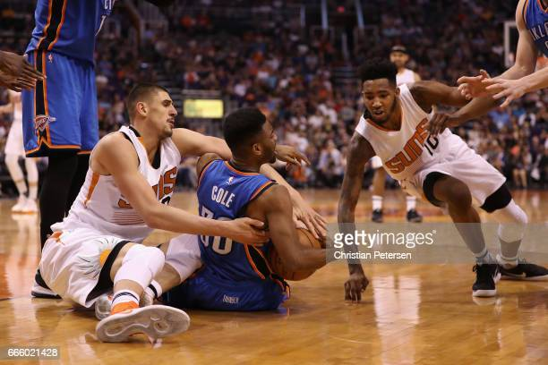 Norris Cole of the Oklahoma City Thunder picks up a loose ball ahead of Alex Len and Derrick Jones Jr #10 of the Phoenix Suns during the NBA game at...