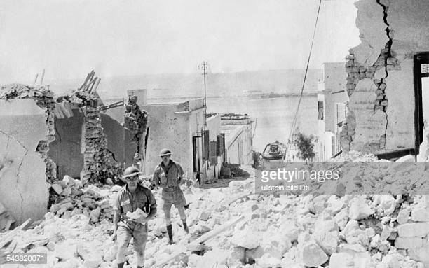 2WW North Africa war theater Germanitalian army Australian soldiers walk through debris after a raid of german bombers on the besieged port town of...