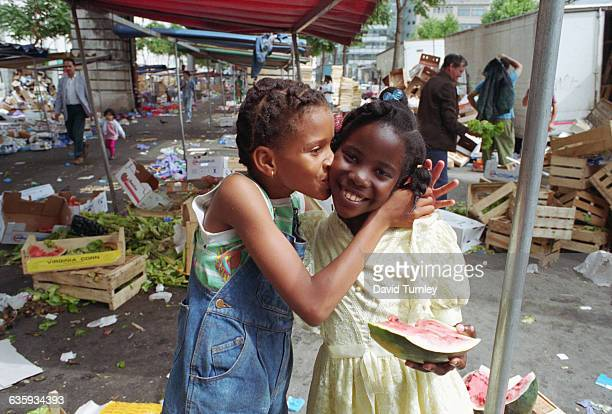 North African girls play in an open air market in La Goutte D'Or an immigrant quarter of Paris France
