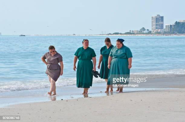 North America USA Florida Sarasota Crescent Beach Siesta Key Amish Women Walking along Water's Edge