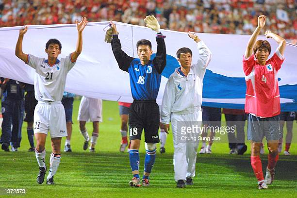 North and South Korean players as well as coaching staff carry the unification flag after their friendly game for unification of both Koreas at the...