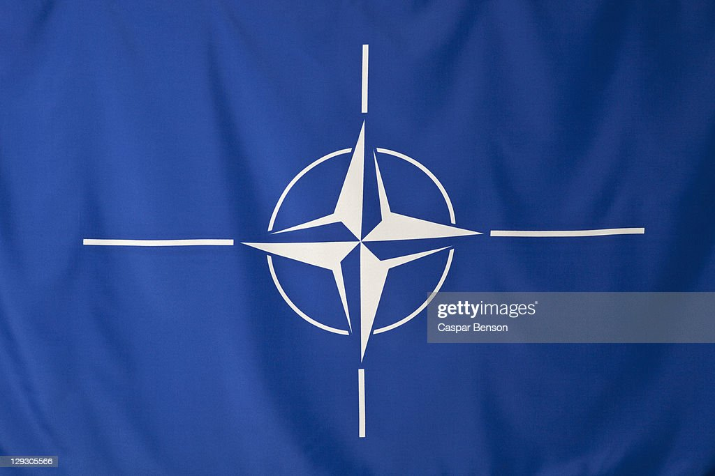 North Atlantic Treaty Organization flag, white compass rose emblem in blue background : Stock Photo