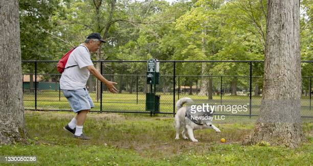 Adam Lee of North Babylon, New York, brings his dog Eve to enjoy the new dog run at Belmont Lake State Park in North Babylon on July 21, 2021.
