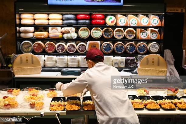 Cheese is prepared at the cheese counter by a store employee inside the Uncle Giuseppe's Marketplace in North Babylon, New York on Dec. 29, 2020.
