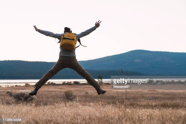USA, North California, rear view of young man on a hiking trip jumping near Lassen Volcanic National Park