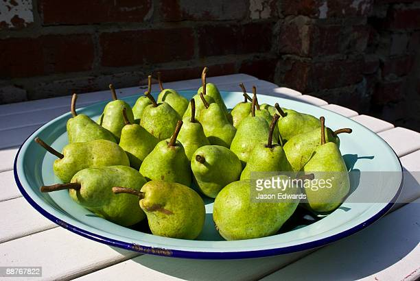 A plate of ripe delicious pears on a platter in a garden.