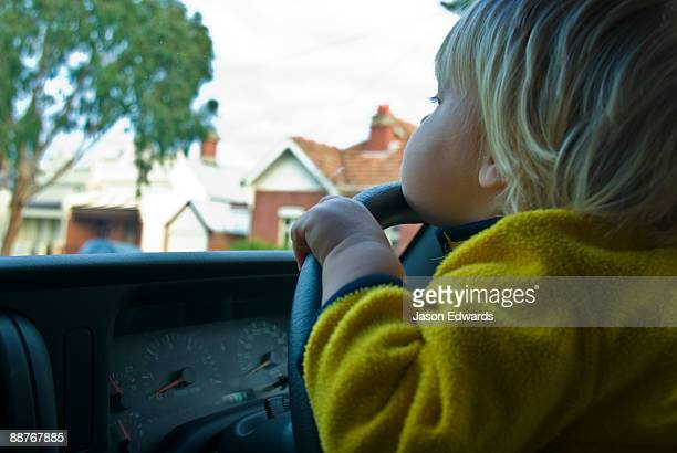 A toddler peers over the steering wheel of an SUV pretending to drive.