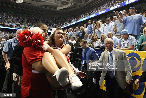 North Carolina head coach Roy Williams facilitates the exit of an injured Radford cheerleader prior to the start of the second half on Thursday,...