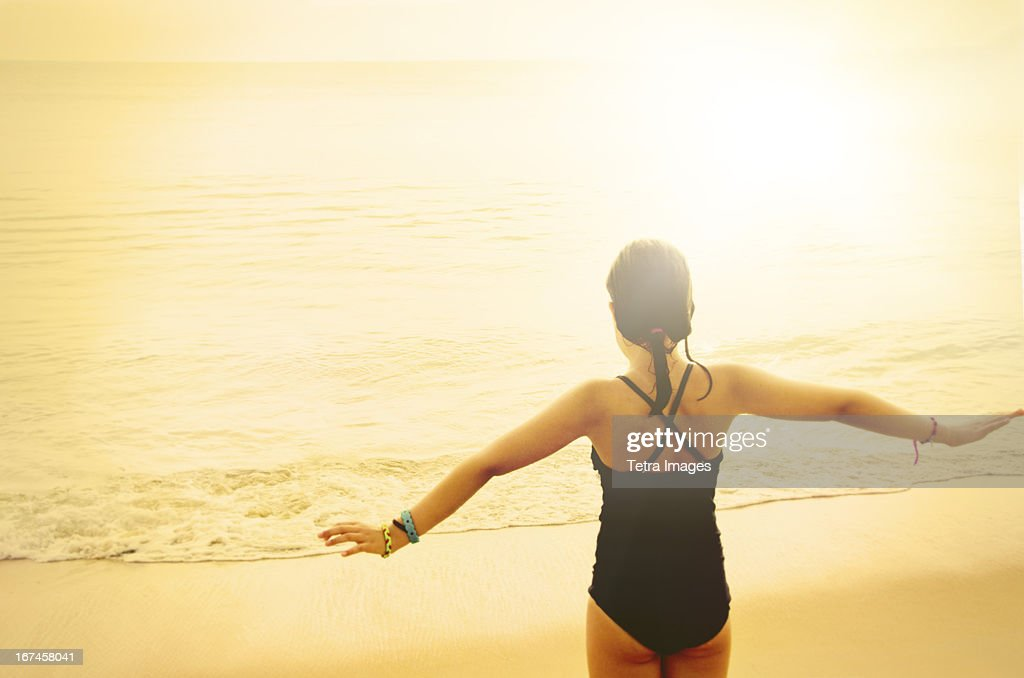 USA, North Carolina, Nags Head, Rear view of girl (8-9) standing with arms raised : Stock Photo