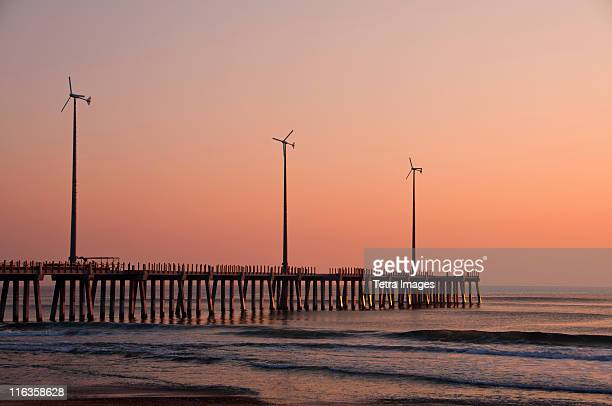 usa, north carolina, outer banks, kill devil hills, pier with wind turbines at sunset - kitty hawk beach stock pictures, royalty-free photos & images