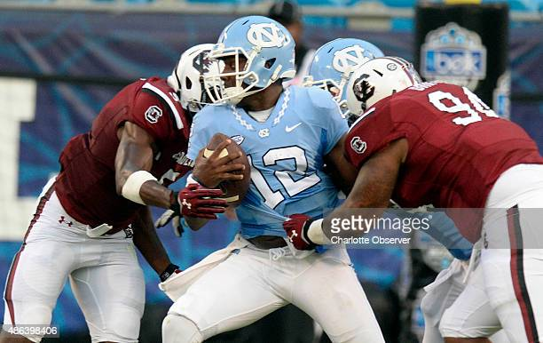 North Carolina quarterback Marquise Williams is sacked by South Carolina's Darius English and Kelsey Griffin during the first half in the Belk...