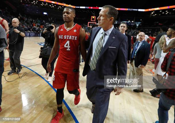 North Carolina State head coach Mark Gottfried walks off the floor with Dennis Smith Jr after a 7561 loss against Clemson in the first round of the...