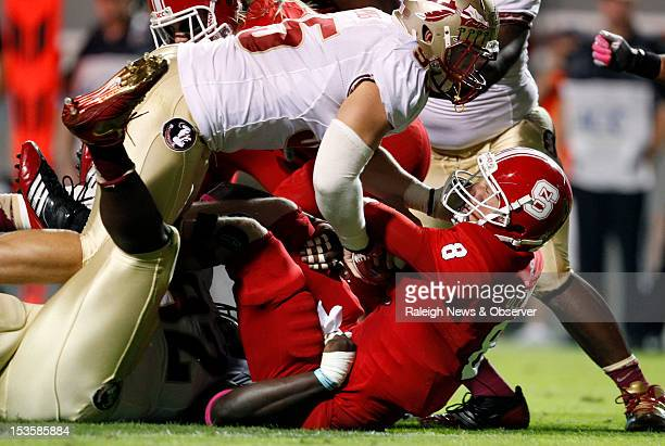 North Carolina State quarterback Mike Glennon is sacked by Florida State defensive tackle Anthony McCloud and Bjoern Werner during the first half at...