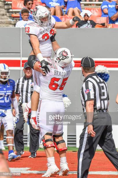 North Carolina State Wolfpack center Garrett Bradbury lifts North Carolina State Wolfpack running back Brady Bodine high into the air after the...