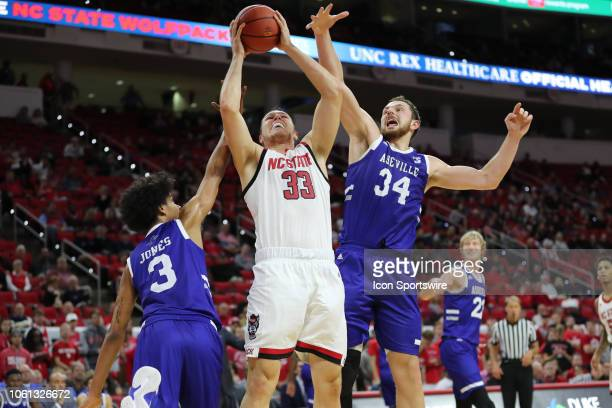 North Carolina State Wolfpack forward Wyatt Walker shoots a basket with North CarolinaAsheville Bulldogs forward Jeremy Peck and North...