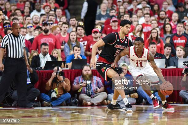 North Carolina State Wolfpack guard Markell Johnson cuts to the inside as Louisville Cardinals forward Anas Mahmoud defends during the men's college...