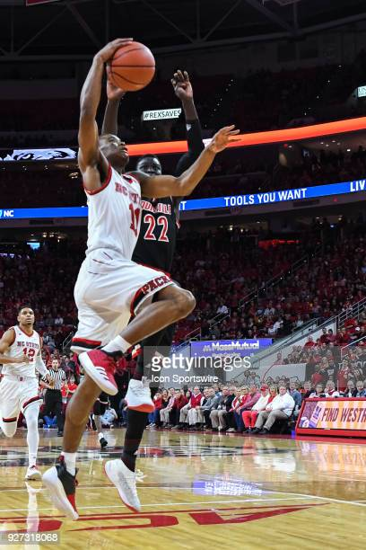 North Carolina State Wolfpack guard Markell Johnson drives to the basket as Louisville Cardinals forward Deng Adel defends during the men's college...