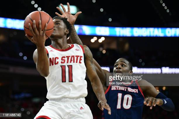 North Carolina State Wolfpack guard Markell Johnson goes in for a layup past Detroit Titans forward Boe Nguidjol during the game between the NC State...